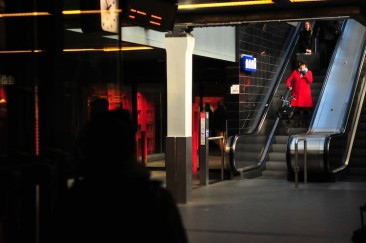 A woman in red descends an escalator at the central train station, Amsterdam.